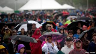 Hundreds of people stand with umbrellas and rain gear in front of a tent