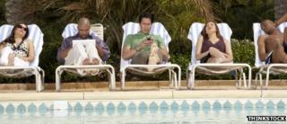 Line of deckchairs with people using laptops and smartphones