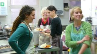 Volunteers prepare meals for clients at Catching Lives