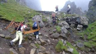 Friends carry dining table on climb near Staffin on Skye