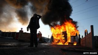 An activist looks on in front of a burning caravan, which was set ablaze by activists to be used as a barricade, as evictions began at Dale Farm travellers camp on 19 October last year
