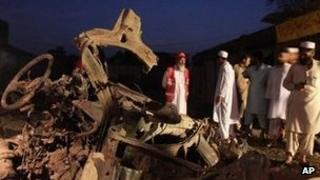 Pakistani rescue workers and investigators look at a vehicle in which a bomb was planted at Mattani, outside Peshawar.