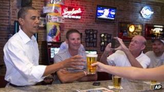 President Barack Obama buys a beer at a pub and grill in Cedar Falls, Iowa, while a campaign bus tour on 14 August 2012