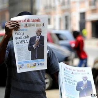 Street-seller in Luanda holds up copy of the state-owned Jornal de Angola daily on 2 August