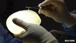 A surgeon holds a defective silicone PIP gel breast implant