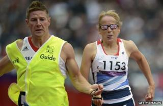 GB's Tracey Hinton (R) runs with her guide Steffan Hughes (L) during the Women's 200 metres T11 Semifinal