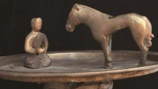 Raised bronze trays featuring a figure kneeling in front of a horse at the Smithsonian Freer and Sackler Asian Art galleries