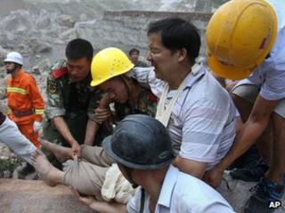 Paramilitary policemen and residents move out an injured man from quake hit Zhaotong town, Yiliang County, in China's southwest Yunnan Province, 8 Sept 2012