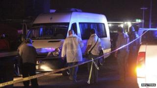 Forensic technicians stand around a white van containing the bodies of several men on a highway on the outskirts of San Luis Potosi, 9 August 2012