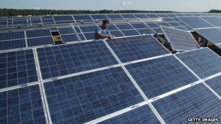 Workers installing panels at a solar park