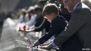 Andrew Timson, 7, etches the name of his late uncle Andrew Fisher during ceremonies marking the 11th anniversary of the 9/11 attacks on the World Trade Center in New York, September 11, 2012.