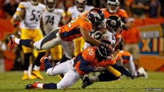 Tight end Heath Miller #83 of the Pittsburgh Steelers makes a reception and is tackled by linebacker Wesley Woodyard #52 and defensive back Mike Adams #20 of the Denver Broncos
