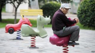 An elderly man rides on a toy horse in Beijing on 9 September 2012