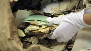 Pulling torn paper fragments from a sack