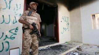 A Libyan soldier guards one of the buildings of the burnt out US consulate in Benghazi, Libya