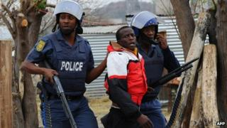 South African police arrest a miner as part of a crackdown in Marikana on Saturday