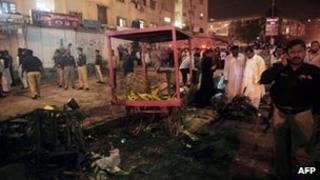 Pakistani security officials scan the site of a bomb explosion in Karachi