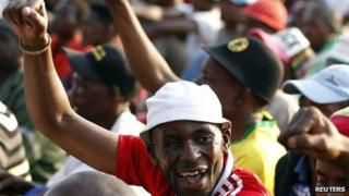 """Striking miners gesture after they were informed of a 22 percent wage increase offer outside Lonmin""""s Marikana mine, 100 km (60 miles) northwest of Johannesburg, September 18, 2012"""