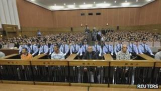 Suspects involved in murders of 13 Chinese sailors on the Mekong River are on trial as police officers sit guard behind them at a court in Kunming, 20 Sept 2012