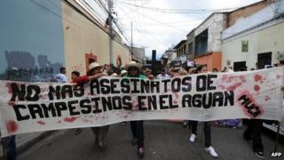 Members of the Peasant Unified Movement (MUCA) of Bajo Aguan, carry mock coffins bearing pictures of murdered mates in land conflict clashes. Sep 15 2012.