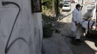 "Forensic technicians remove a body from a crime scene near a wall spray painted with the ""Z"" symbol of the Zetas drug cartel, in Monterrey."