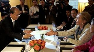 Burma's President Thein Sein hands US Secretary of State Hillary Clinton an envelope as they meet in New York on 26 September 2012