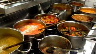 Curries being cooked on large stove