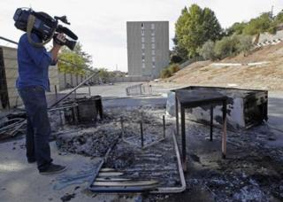 A cameraman films the charred remains of the Roma camp in Marseille, 28 September