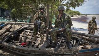 In this Wednesday, Dec. 14, 2011 file photo, Kenyan army soldiers sit on a currently unused fishing boat on the white sand shore of the seaside town of Bur Garbo, Somalia.