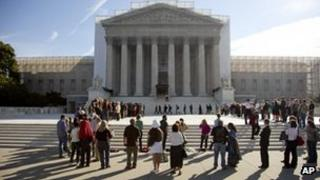 People wait outside the US Supreme Court in Washington, DC, 1 October 2012