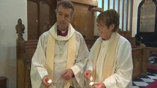 Bishop of Bangor, Andy John, with Revd Kathleen Rogers, priest-in-charge, lighting candles at a vigil for April Jones at St Peter's Church, Machynlleth, on Wednesday
