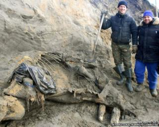 Researchers pose with the mammoth remains