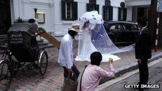A photographer positions a bride for a picture for her wedding photo album in front of a colonial style hotel, rickshaw and old cars in downtown Hanoi on August 26, 2010.