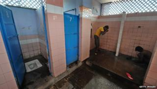 Men washing in a toilet at a railway station in New Delhi