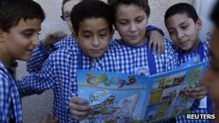 Children read an edition of Qaws Quzah (Rainbow) magazine in Tunis