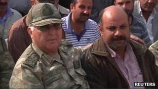 General Ozel with arm around man who's wife and children were killed