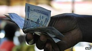 A woman holding Ugandan shilling notes in Kampala, May 2011