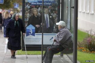 Elderly people at a bus stop with an election poster in Vilnius, 2 October