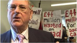 Councillor Peter Jones in front of protesters