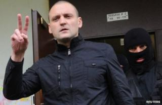 Sergei Udaltsov flashes a victory sign as he is led away in Moscow, 17 October