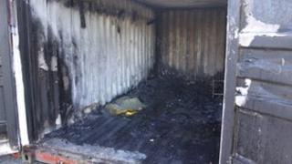 Inside an arson-damaged shipping container