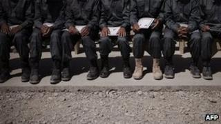 Afghan police graduates sitting on a bench