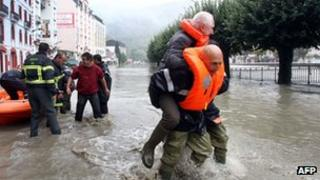 A rescuer carries a man on his back in Lourdes. Photo: 20 October 2012