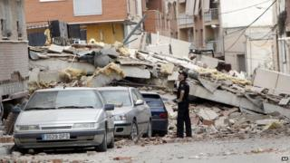 Police officer inspects earthquake damage