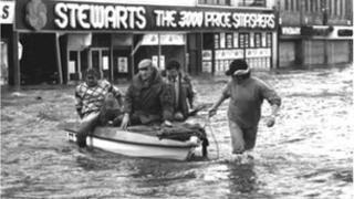 People in boat in flooded street