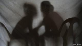 Silhouette of two girls rescued from a sex trafficking ring talking behind a screen