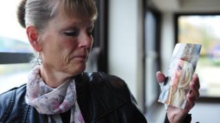 Sue Johnson holding a picture of Nicola Johnson