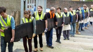 Project team carry the bog oak to the kiln