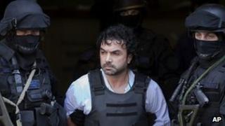 Policemen escort Henry de Jesus Lopez after his arrest