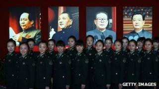 Female soldiers pose for photos in front of the portraits of China's President Hu Jintao and former President Jiang Zemin at an exhibition in Beijing, 31 Oct 2012